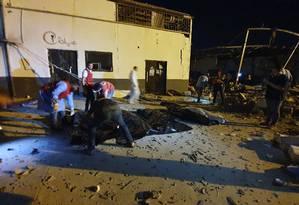Equipes de emergência retiram os corpos das 40 pessoas mortas no ataque aéreo contra um abrigo para imigrantes nos arredores de Tripoli. 120 pessoas estavam no local. Foto: MAHMUD TURKIA / AFP