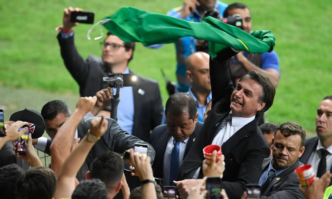 Jair Bolsonaro agita a bandeira brasileira no intervalo do jogo entre Brasil e Argentina na Copa América Foto: MAURO PIMENTEL / AFP