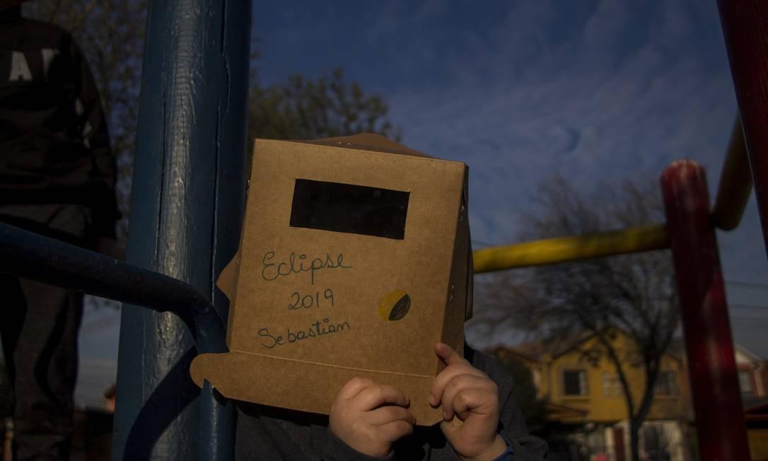 Para assistir ao eclipse, porém, é preciso tomar uma série de precauções. A principal delas é utilizar uma proteção aos olhos e não olhar diretamente para o Sol. Essa criança, na província de Maipú, Chile, personalizou seu visor. Foto: NurPhoto / NurPhoto via Getty Images