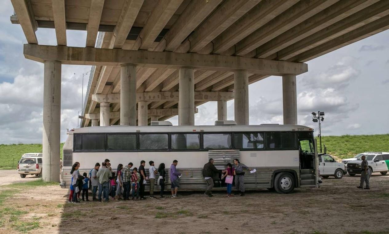 Imigrantes esperam para ser transportados a um centro de processamento da patrulha fronteiriça dos EUA depois de se entregarem aos agentes de fronteira após atravessarem o Rio Grande em busca de asilo político nos Estados Unidos Foto: JOHN MOORE / AFP