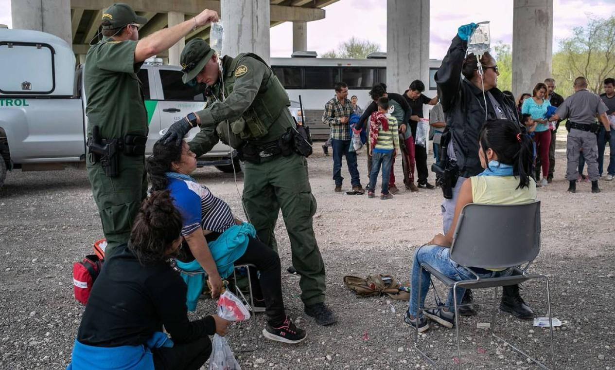 Um médico da Patrulha Fronteiriça dos EUA trata um imigrante exausto pelo calor em McAllen, Texas Foto: JOHN MOORE / AFP