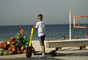 Menino ainda andava com uma das patinetes na orla da Praia de Copacabana nesta quarta-feira. Com nova regulamentação, menores de 18 não poderão pilotar as scooters Foto: Antonio Scorza / Agência O Globo