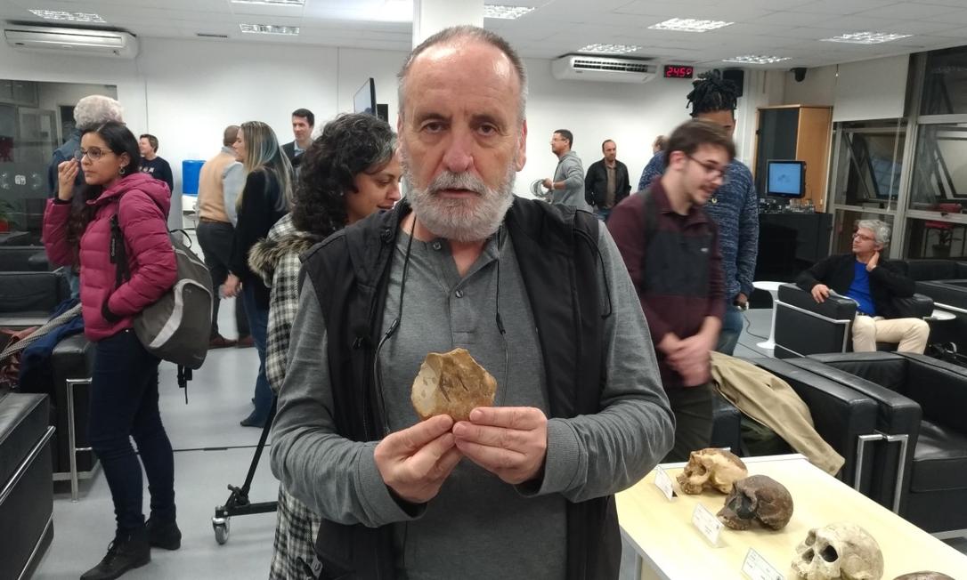 O biólogo, arqueólogo e antropólogo evolutivo Walter Neves, da USP, segura um dos artefatos que permitiram a descoberta da presença de ancestrais humanos fora da África há 2,4 milhões de anos