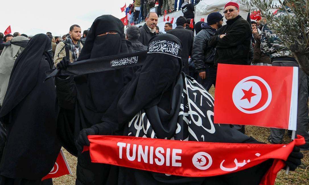Muçulmanas salafistas tunisianas usam niqab durante manisfestação em 2012, em frente à sede da TV estatal, em Túnis Foto: FETHI BELAID / AFP