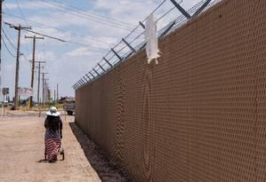Mulher caminha ao lado de uma cerca perto de abrigo da Patrulha da Fronteira, em Clint Foto: LUKE MONTAVON / AFP