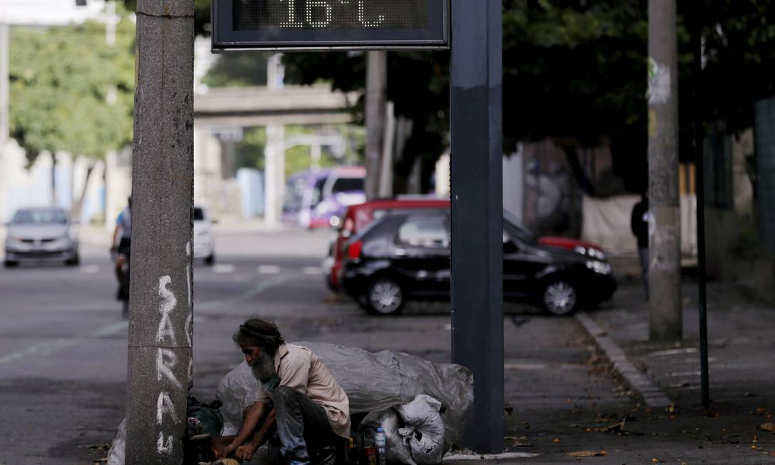 Morador em situação de rua aquece comida na Rua Benedito Hipólito, no Centro do Rio Foto: Gabriel de Paiva / Agência O Globo