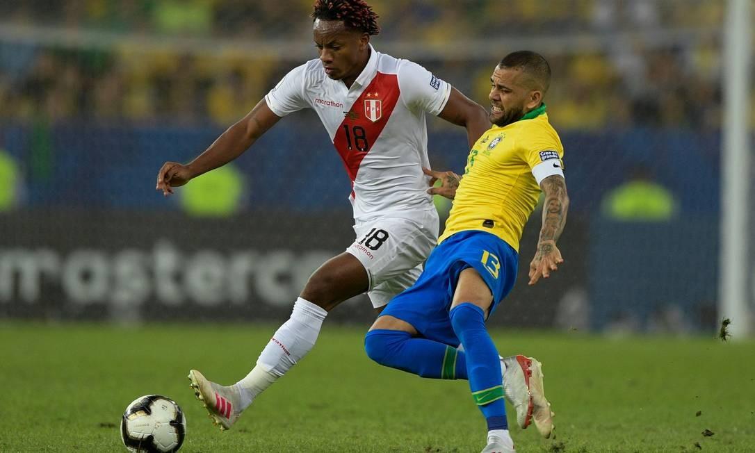 Andre Carrillo e Daniel Alves disputam a posse de bola durante primeiro tempo da partida entre Brasil e Peru Foto: JUAN MABROMATA / AFP