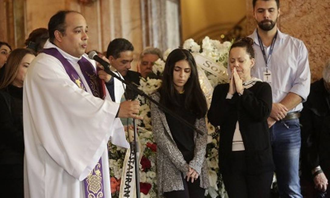Padre Omar reza no velório de João Gilberto, ao lado de das filhas do compositor, Luísa e Bebel Foto: Marcos Ramos / Agência O Globo