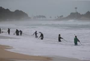 Com o mar da ressaca, garimpeiros em Ipanema enfrentam a mau tempo na busca por material de valor perdido entre as ondas. Um deles chega a usar uma barra com detector de metal Foto: Fabiano Rocha / Agência O Globo