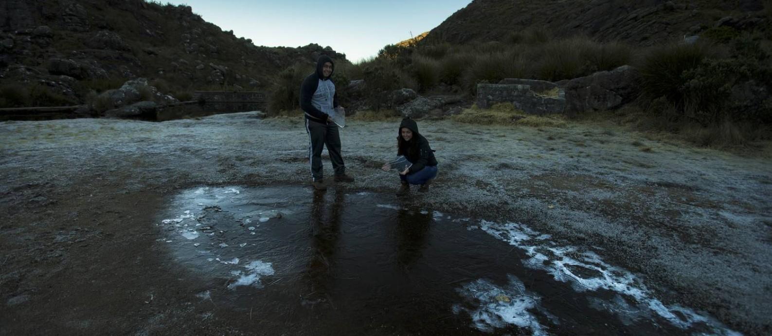 Os turistas Liliam e Marcelo Lois, com pedacos de gelo nas mãos, observam um braço de rio congelado e a vegetação gelada Foto: Antonio Scorza / Agência O Globo
