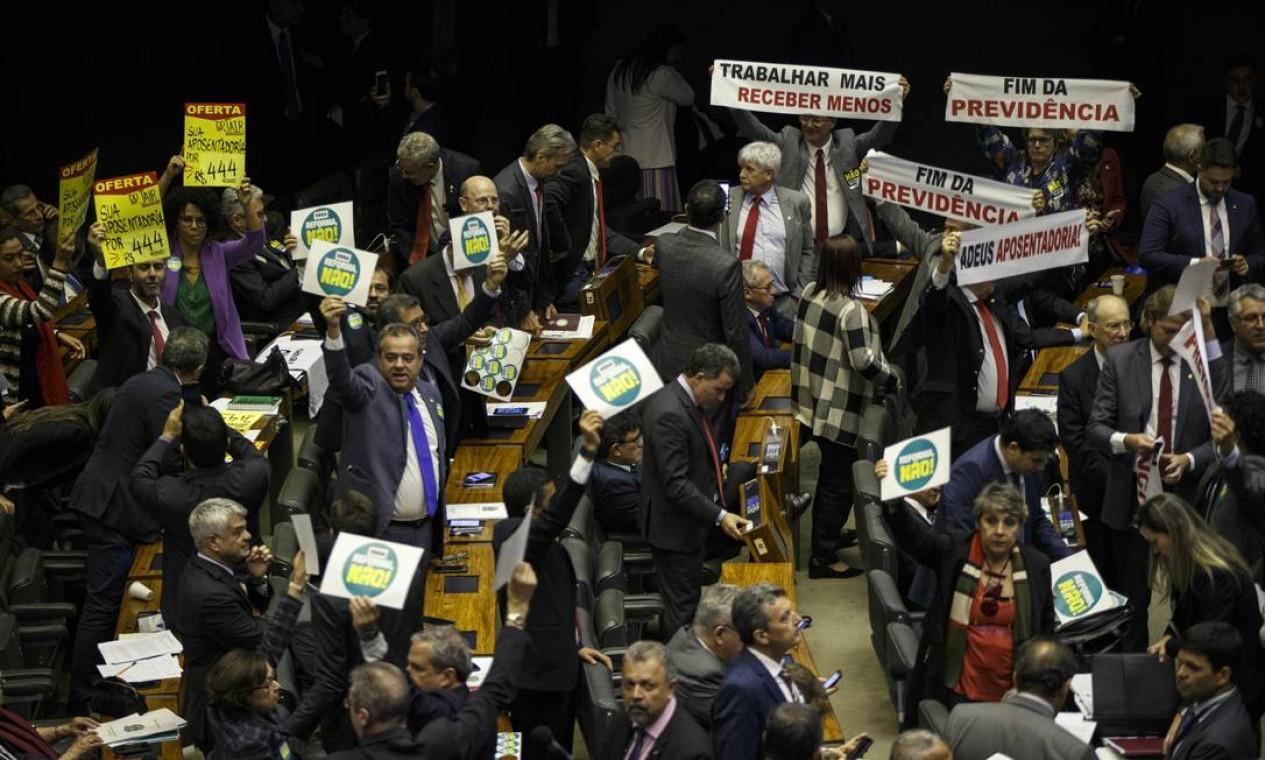 Deputados contrários à reforma da Previdência levantam cartazes no plenário da Câmara em sessão que durou até a madrugada desta quarta-feira Foto: Daniel Marenco / Agência O Globo