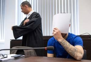 Ali Bashar, cobrindo o rosto, durante julgamento que determinou sua sentença na Alemanha Foto: BORIS ROESSLER / AFP