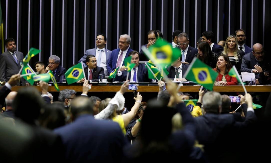 O presidente da Câmara dos Deputados, Rodrigo Maia, é visto entre bandeiras do Brasil levantandas por apoiadores do governo e da reforma da Previdência que será votada nesta quarta-feira, no plenário da Casa Foto: ADRIANO MACHADO / REUTERS
