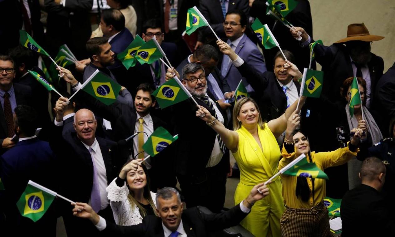 Apoiadores do governo e da reforma exibem bandeiras do Brasil durante sessão que discute o texto-base da PEC da Previdência Foto: ADRIANO MACHADO / REUTERS