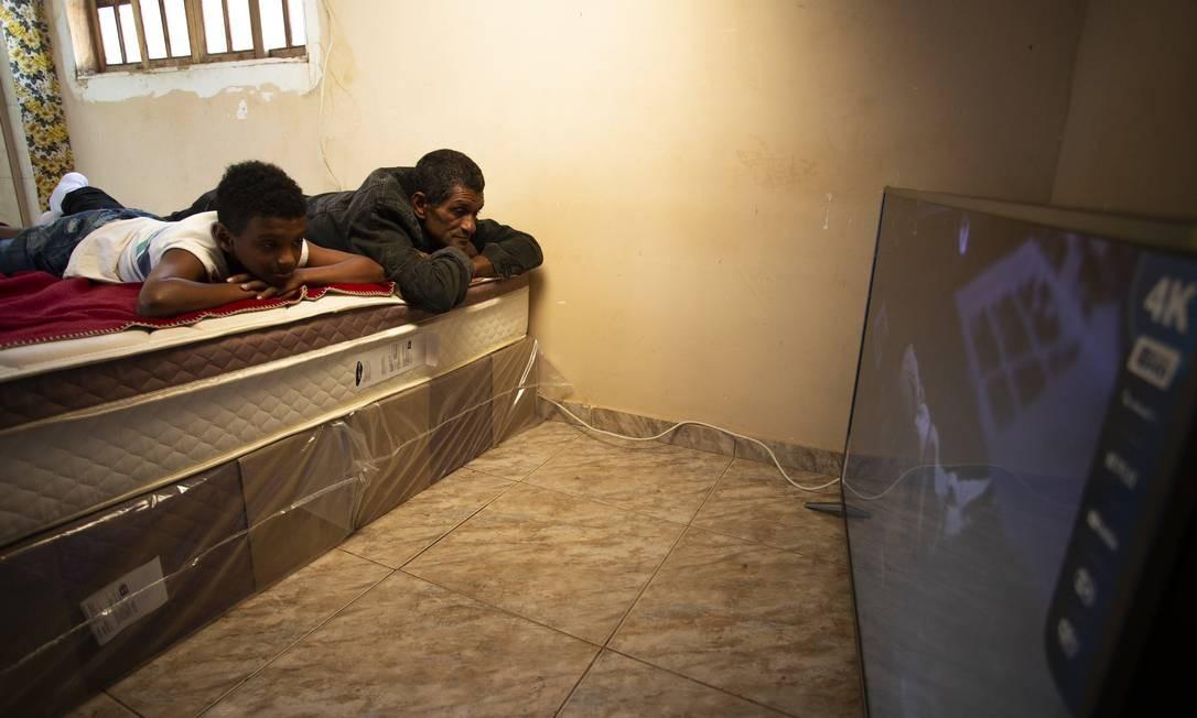 Varlei e Darlei aproveitam o novo espaço para assistir televisão. Quartos ainda terão mobília comprada Foto: ROBERTO MOREYRA / Agência O Globo
