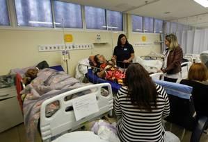 A secretária de Saúde, Beatriz Busch (camisa azul marinho) visita pacientes, que ainda usavam roupa de cama trazida de casa, nesta sexta-feira, na sala amarela da emergência Foto: Divulgação/SMS