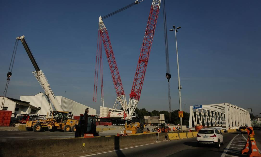 Os guindastes já estão posicionados para erguer a ponte Foto: BRENNO CARVALHO / Agência O Globo