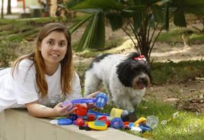 Plástico. Alice com as tampinhas doadas e a cadela Chiclete: peças são vendidas e valor arrecado é doado a ONGs Foto: Fábio Guimarães / Agência O Globo