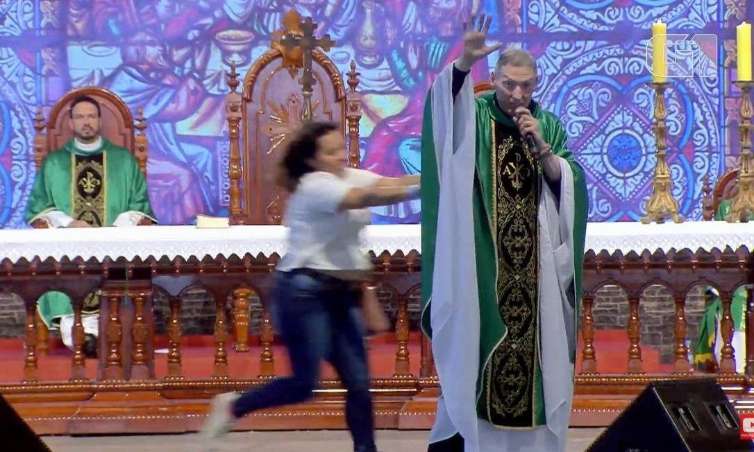 Mulher invadiu palco e empurrou o padre por trás. Foto: Reprodução/Youtube
