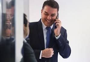 O senador Flávio Bolsonaro sorri enquanto fala no celular, durante cerimônia de posse do novo presidente do BNDES nesta terça-feira, em Brasília Foto: Jorge William / Agência O Globo