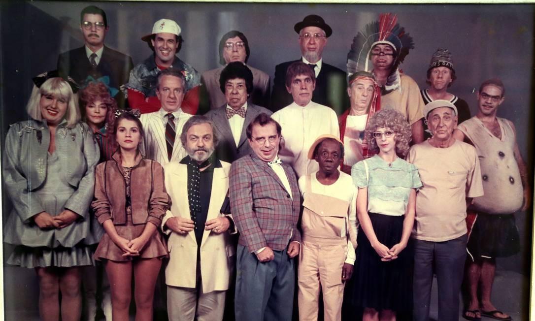"""Elenco da """"Escolinha do Professor Raimundo"""" na década de 1990. Na primeira fileira: Cláudia Jimenez (Dona Cacilda), Tássia Camargo (Marina da Glória), Antônio Pedro (Bicalho), Castrinho (Geraldo), Grande Otelo (Eustáquio), Stella Freitas (Cândida) e Brandão Filho (Sandoval Quaresma); na segunda, Zezé Macedo (Dona Bela), Rogério Cardoso (Rolando Lero), Walter D'ávilla (Baltazar da Rocha), Antônio Carlos Pires (Jesilino Barbacena), Orlando Drummond (Seu Peru) e Lug de Paula (Seu Boneco); na terceira fileira, Nizo Neto (Senhor Ptolomeu), Sérgio Mallandro (Mallandro), Mário Tupinambá (Bertoldo Brecha), Marcos Plonka (Samuel Blaustein), Jaime Filho (Suppapau Uaçu) e Olney Cazarré (João Bacurinho) Foto: Reprodução"""