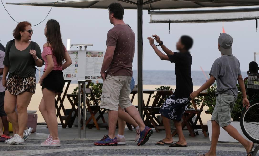 Menino se aproxima da vítima na altura do Posto 3 Foto: Domingos Peixoto / Agência O Globo