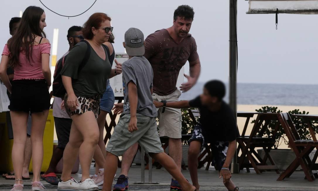 Menino de boné parece dar cobertura a jovem de blusa preta Foto: Domingos Peixoto / Agência O Globo