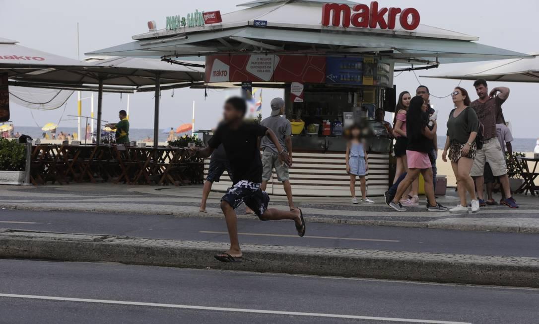 Após ação, menino atravessa Avenida Atlântica correndo Foto: Domingos Peixoto / Agência O Globo