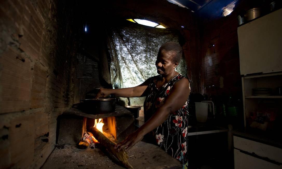 Moradora da comunidade Vale dos Eucaliptos, no Rio, prepara comida em fogão a lenha por falta de dinheiro para comprar gás. Números do Pnad mostram que, por causa da crise econômica, aumentou o número de famílias que usam a lenha para cozinhar Foto: Márcia Foletto / Agência O Globo