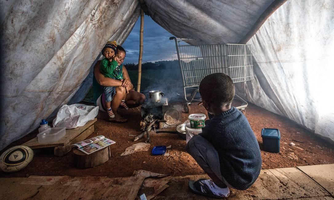 Segundo a Comissão Econômica para a América Latina, 5,9% dos brasileiros vivem na miséria. Em Brasília, mulher cozinha com os filhos seus dois filhos depois de ter os benefícios do Bolsa Família e aluguel social cortados Foto: André Coelho / Agência O Globo