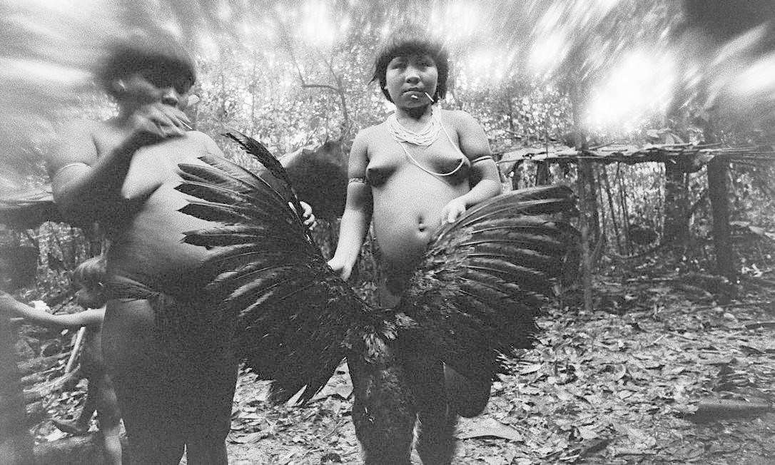 Pássaro negro. As índias Candinha e Mariazinha Korihana limpam um mutum Foto: Claudia Andujar / Divulgação