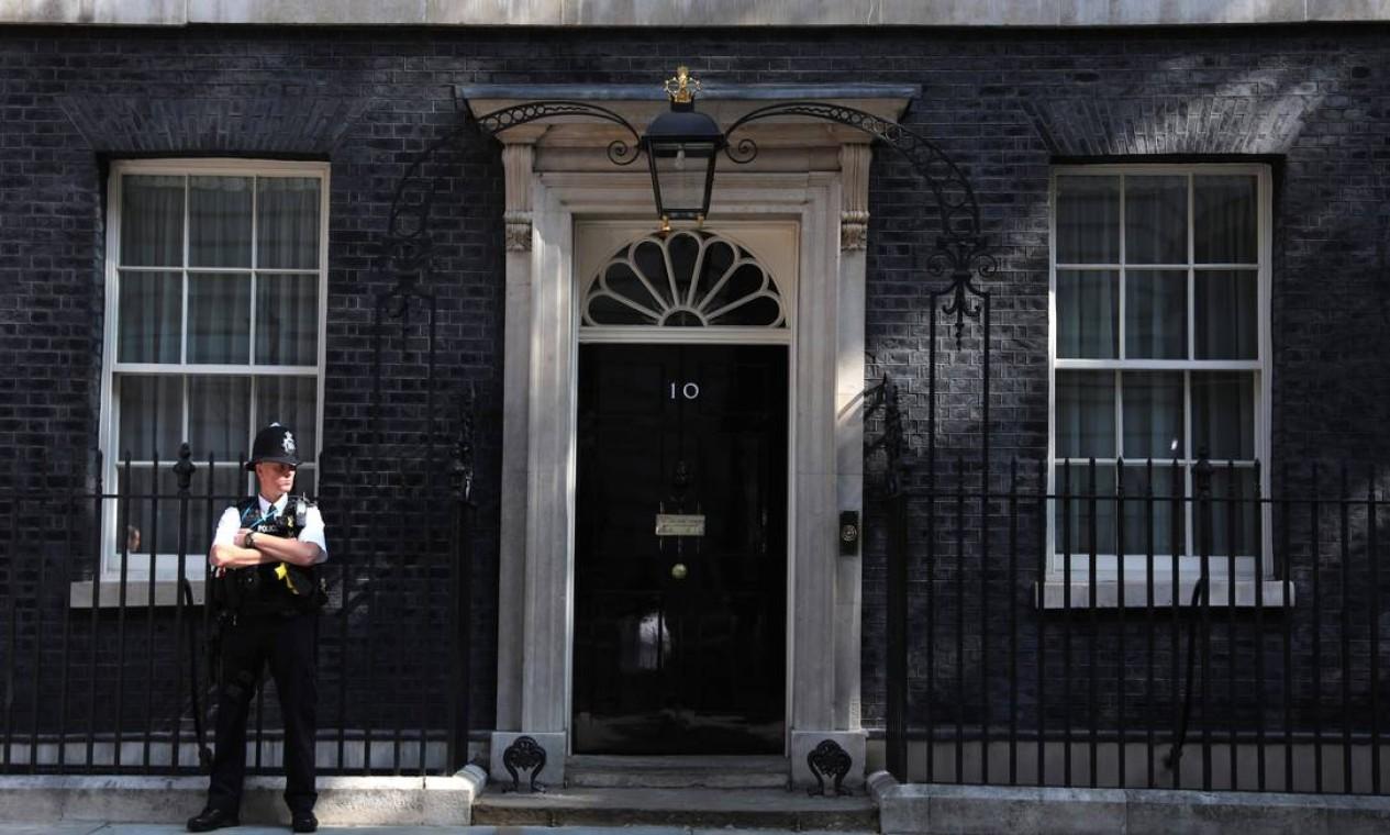 Um policial fica de guarda do lado de fora do número 10 da rua Downing, no centro de Londres. O prédio é a residência oficial e o escritório do primeiro-ministro do Reino Unido Foto: ISABEL INFANTES / AFP