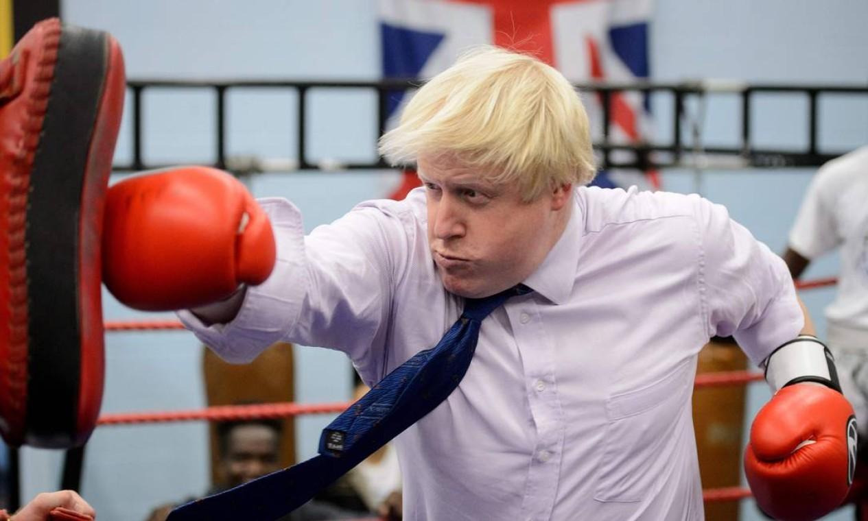 Ex-prefeito de Londres, Boris Johnson foi escolhido premier do Reino Unido com 66,3% dos quase 160 mil votos do Partido Conservador. Nesta foto, tirada em 28 de outubro de 2014, enquanto governava a capital britânica, Johnson treina boxe durante sua visita à Academia Luta pela Paz em North Woolwich Foto: LEON NEAL / AFP