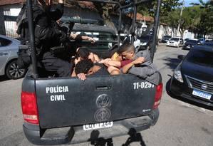 Os presos chegando à DHNSG Foto: Fabiano Rocha / Agência O Globo