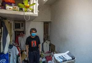 Kenneth Leung num apartamento subdividido no bairro de Sham Shui Po, em Hong Kong Foto: LAM YIK FEI / NYT