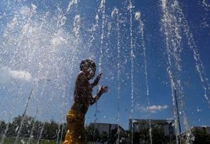 Criança se refresca em uma fonte durante um dia quente de verão em Berlim, Alemanha Foto: FABRIZIO BENSCH / REUTERS