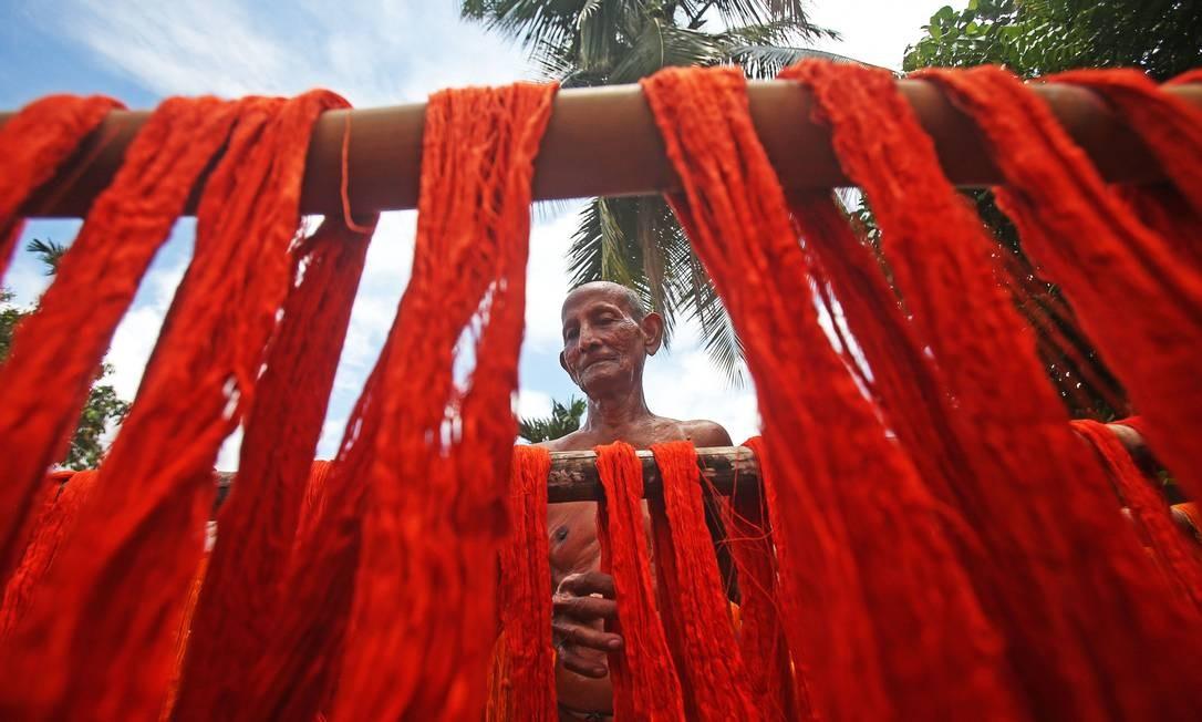 Trabalhador pendura fios tingidos para secar em uma fábrica têxtil nos arredores de Agartala, Índia Foto: PRASANTA DEY / AFP
