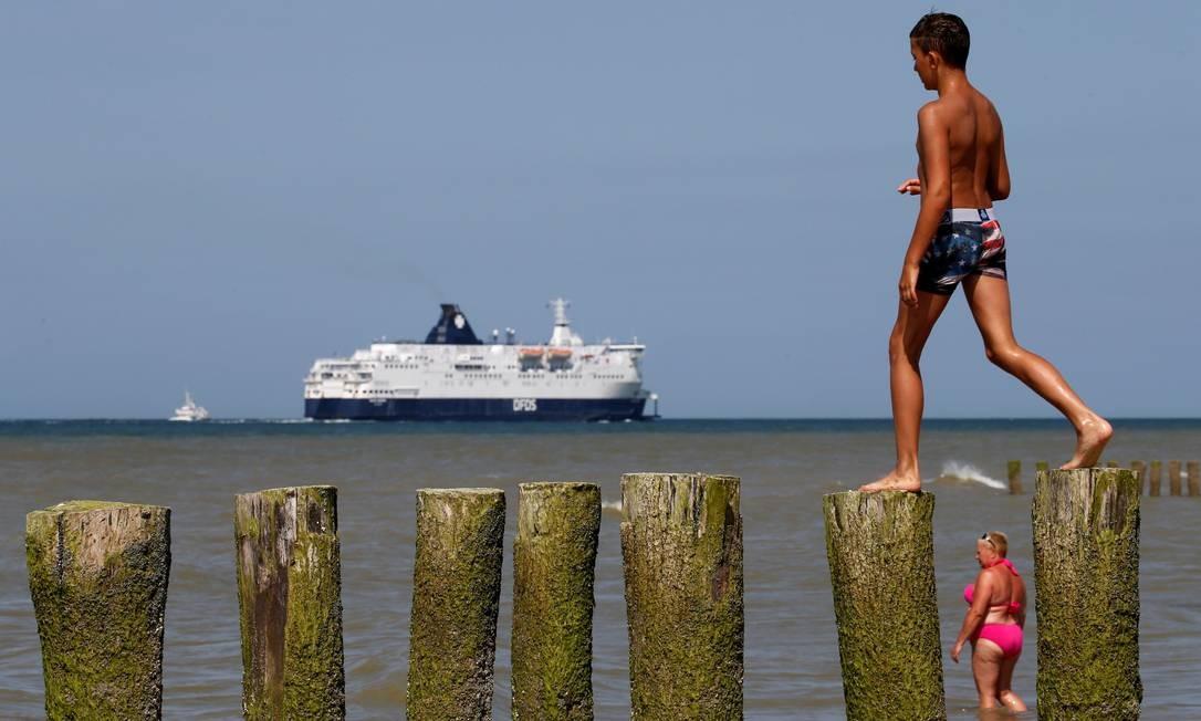 Pessoas se refrescam no mar em um dia quente de verão enquanto barco navega em Sangatte, França Foto: PASCAL ROSSIGNOL / REUTERS