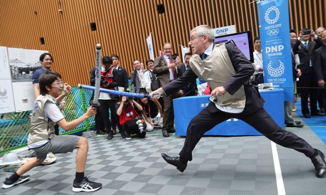 O presidente do COI, Thomas Bach, simula uma luta de esgrima com o estudante japonês Yui Hashimoto durante evento que marcou a contagem regressiva de um ano para o início dos Jogos Olímpicos de Tóquio Foto: KOJI SASAHARA / AFP