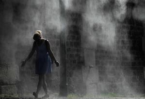 Uma pedestre se refresca nos jatos de água públicos às margens do rio Sena, em Paris; Europa enfrenta maiores temperaturas já registradas Foto: PHILIPPE LOPEZ / AFP