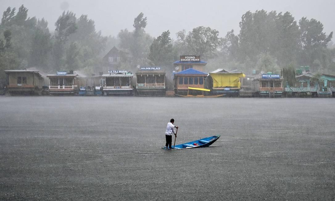 Morador rema sobre um barco no Lago Dal durante uma forte chuva em Srinagar, na Índia Foto: TAUSEEF MUSTAFA / AFP