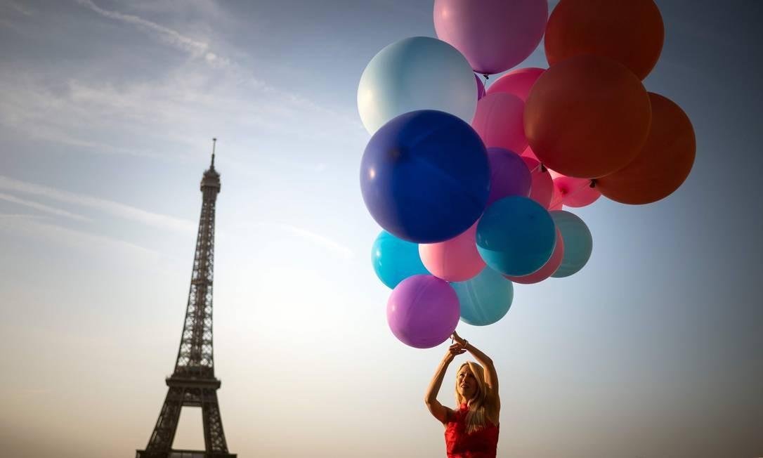 Uma mulher posa com balões em frente à Torre Eiffel, em Paris, nesta quinta-feira (25), quando uma onda de calor atinge a capital francesa. Depois que todos os recordes de temperaturas foram batidos na Bélgica, Alemanha e Holanda ontem, Grã-Bretanha e Paris também experimentam as temperaturas mais altas de todos os tempos Foto: LIONEL BONAVENTURE / AFP