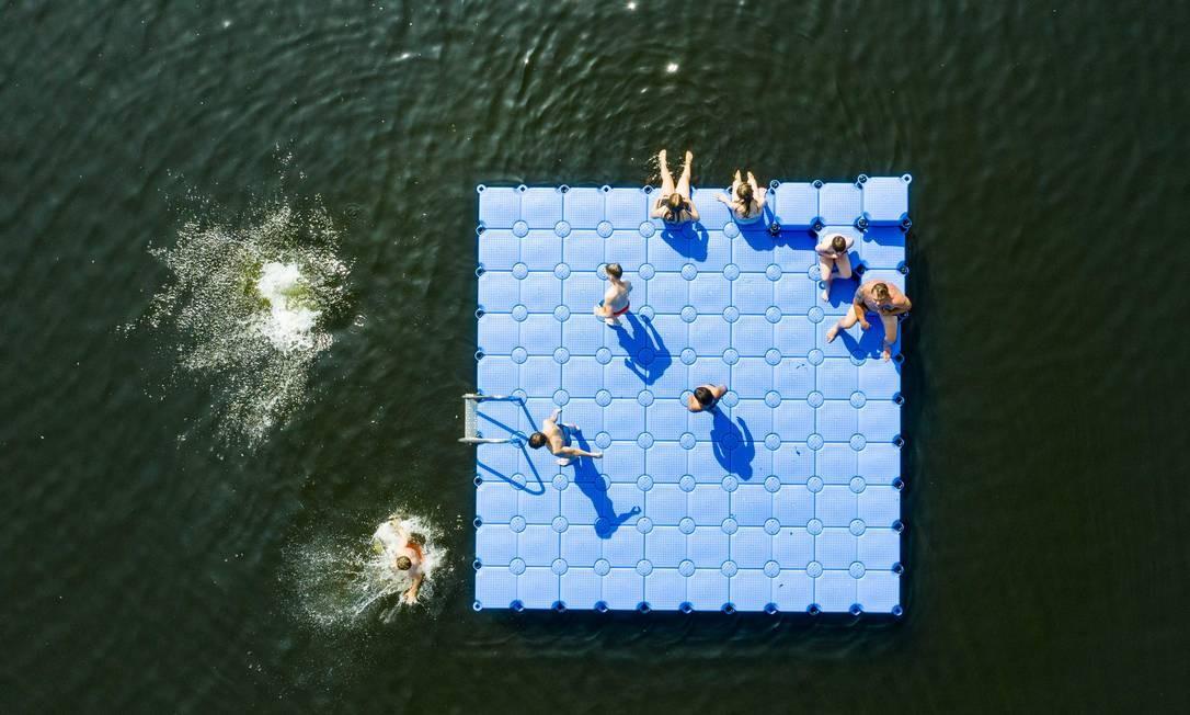 Pessoas brincam e se refrescam sobre uma estrutura flutuante no Lago Altwarmbuechener See, em Hanover, norte da Alemanha, onde as temperaturas estão previstas para chegar a 39°C Foto: CHRISTOPHE GATEAU / AFP