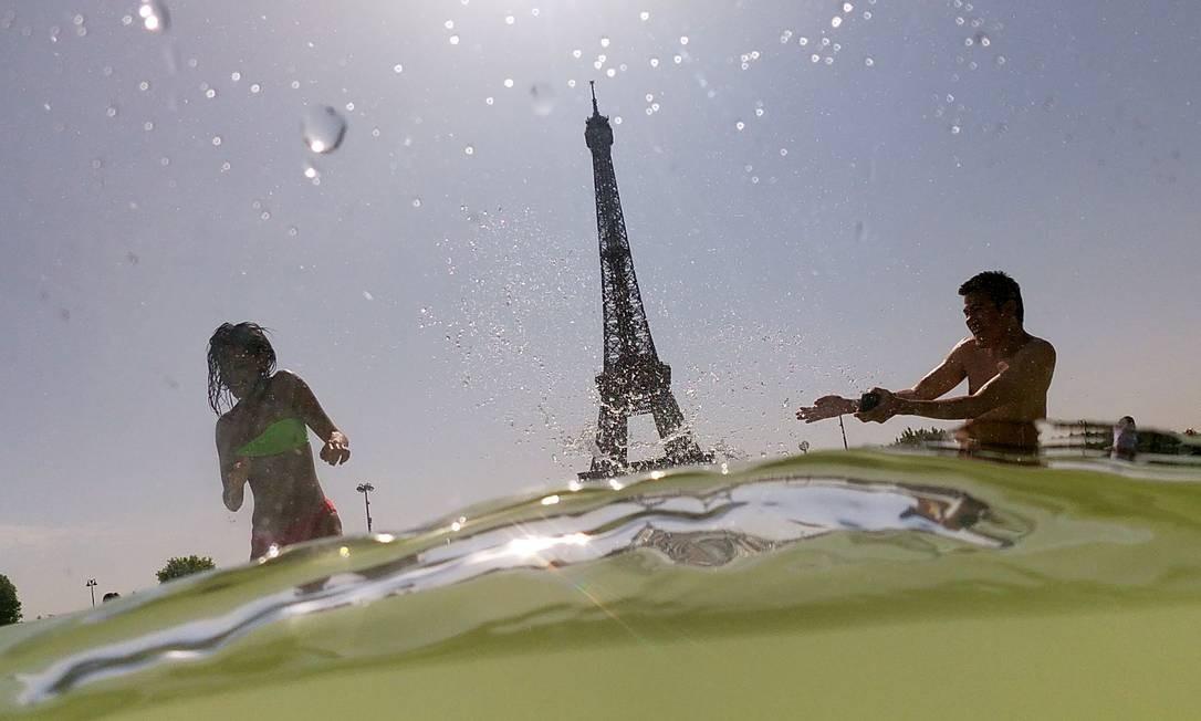 Pessoas se refrescam nas fontes do Trocadero, perto da Torre Eiffel, em Paris Foto: DOMINIQUE FAGET / AFP