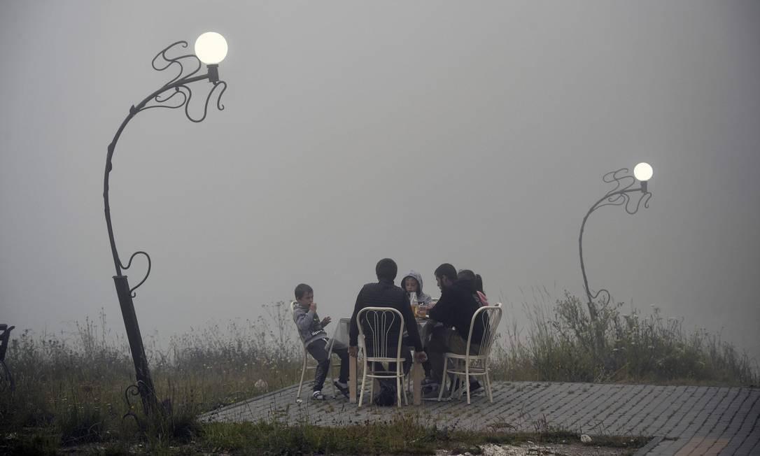 Na Tchechênia, uma família janta em meio a um nevoeiro no clube de iates Kazenoy, no distrito de Vedeno Foto: ALEXANDER NEMENOV / AFP