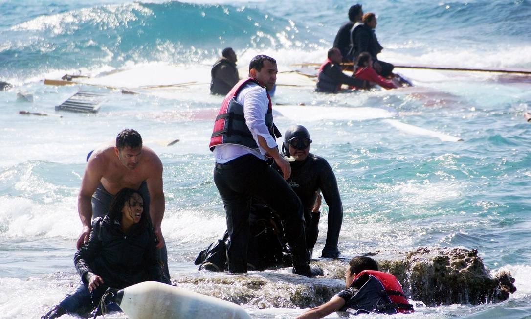 Moradores locais e equipes de resgate ajudam imigrante depois que um barco afundou na ilha de Rhodes, no sudeste da Grécia, em 20 de abril de 2015. A tentativa de entrar ilegalmente na europa resultou na morte de três pessoas, incluindo uma criança, quando o barco, com mais de 80 imigrantes, afundou Foto: Argiris Mantikos / AFP