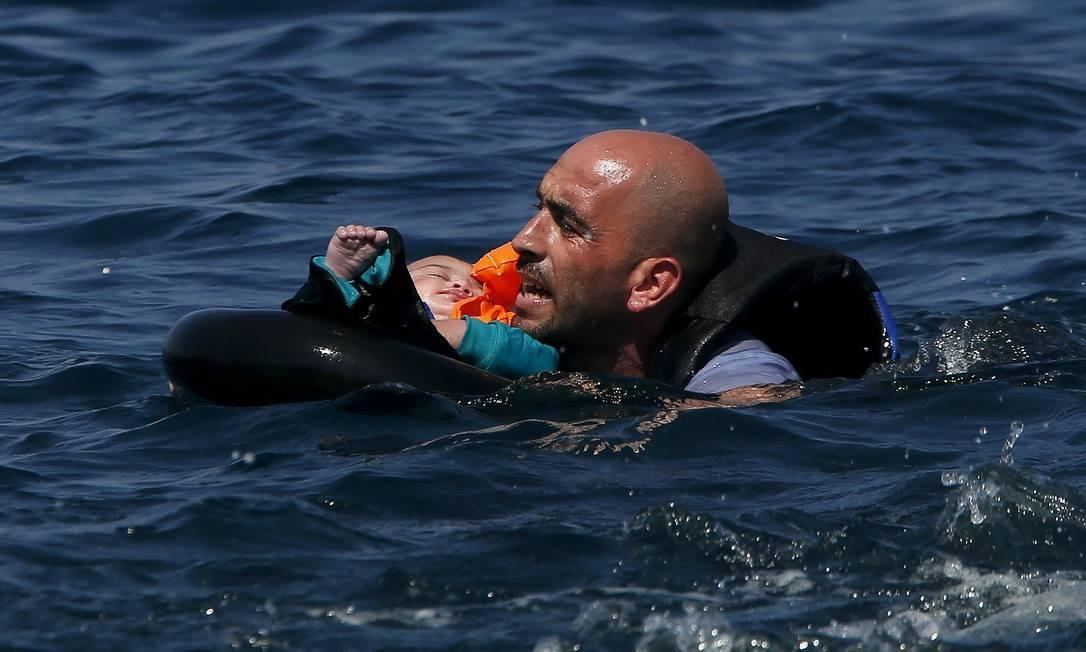 Refugiado sírio nada segurando um bebê em direção à costa depois que seu barco se esvaziou cerca de 100 metros antes de chegar à ilha grega de Lesbos, em 13 de setembro de 2015. Quase metade dos que atravessam o Mediterrâneo são sírios que fogem da guerra civil, segundo a agência de refugiados da ONU Foto: ALKIS KONSTANTINIDIS / Reuters