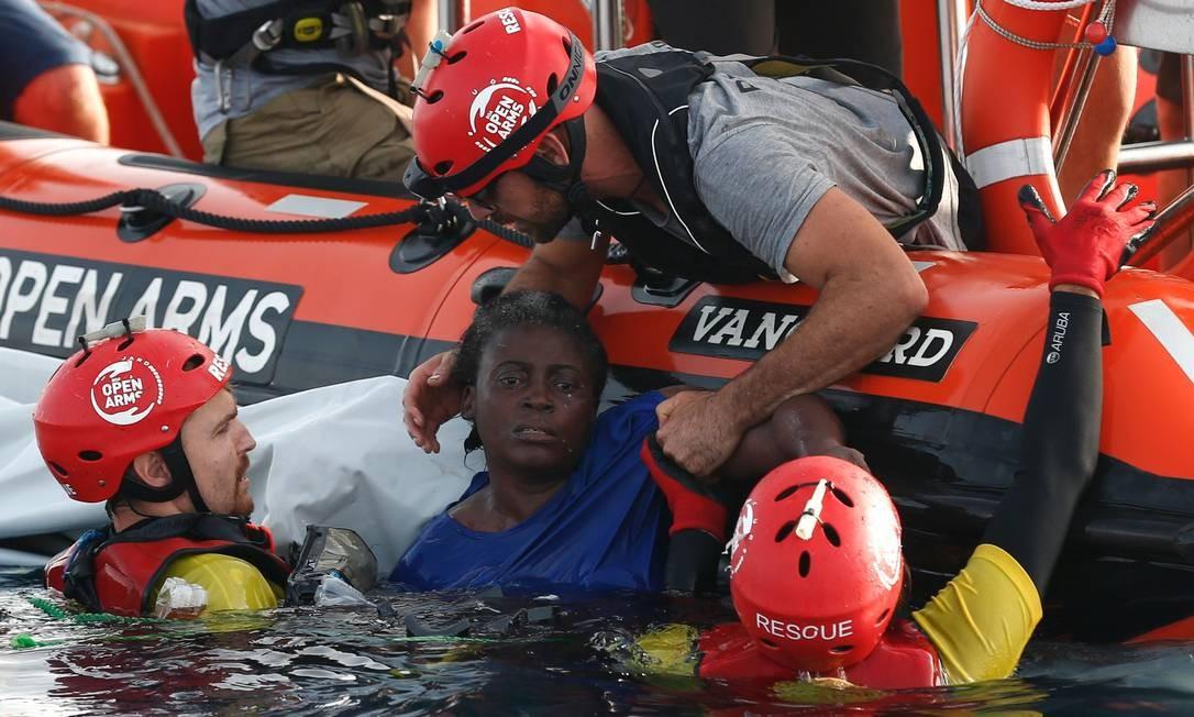 Membros da ONG Proactiva resgatam uma mulher no mar Mediterrâneo a cerca de 135 quilômetros da costa da Líbia, em 17 de julho de 2018 Foto: PAU BARRENA / AFP