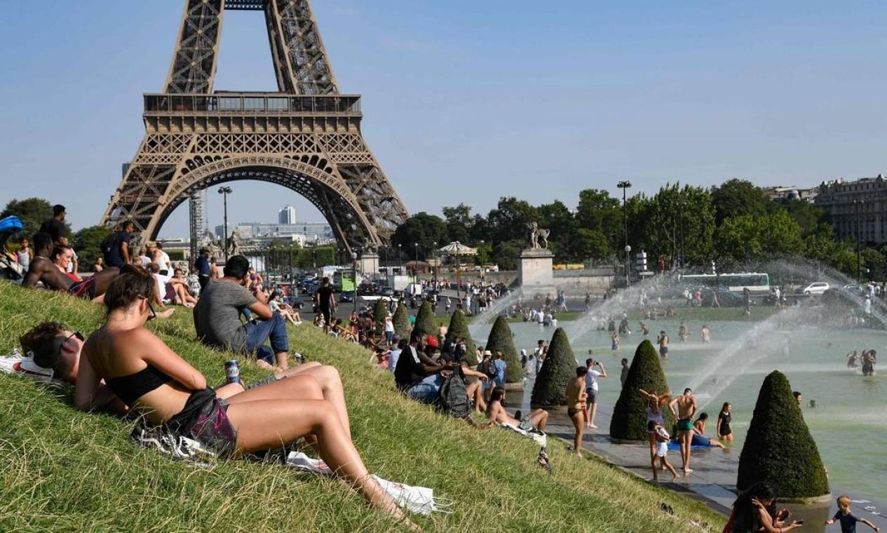 Pessoas se refrescam nas fontes do Jardim do Trocadero, com a Torre Eiffel ao fundo Foto: BERTRAND GUAY / AFP