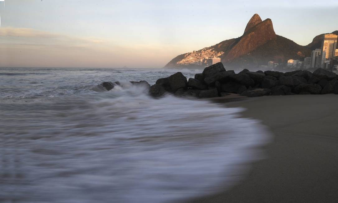 A luz captada nesta imagem mostra que o sol vem surgindo no amanhecer na Praia do Leblon Foto: Custódio Coimbra / Agência O Globo